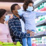 família de máscara fazendo compras representando as vendas no supermercados