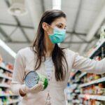 Mulher pegando produto na gôndola mostrando o controle de estoque para supermercados